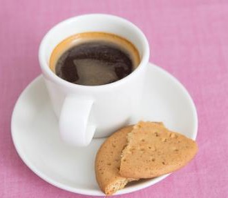 A cup of coffee and cookies on a pink surface.