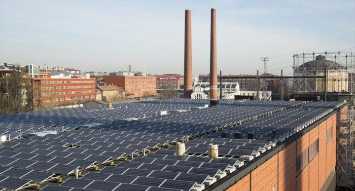 O telhado de um prédio no bairro Suvilahti, em Helsinque, coberto com 1194 painéis solares. Ao fundo, o antigo gasômetro pode ser visto.