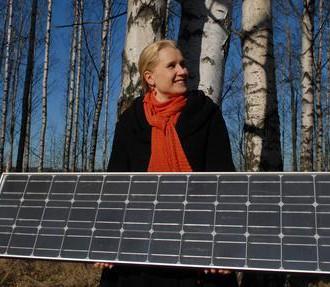 Posando com um painél solar: Karoliina Auvinen da Escola de Negócios da Universidade Aalto, líder do projeto FinSolar, acredita que a Finlândia precisará de uma vasta paleta de energia renovável no futuro.