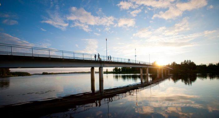 Foto da ponte de Oulu, tirada durante a noite, mostra que o sol não se põe ao norte da Finlândia por alguns meses durante o verão, fazendo do país um ótimo lugar para a energia solar.