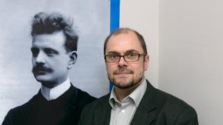 """自1997年以来,蒂莫·维尔塔宁便在芬兰国家图书馆担任西贝柳斯作品的主编。他认为,在这位天才作曲家生日之际,他应当会想听到,自己那些为世人欣赏的作品已被作为重要出版物收集成册。目前,在他全部的52首作品中,已有26部被编纂出版。""""如果将所有这些出版的曲目献给他,并向他承诺,所有余下的作品也会一一出版,他一定会很高兴的吧。"""""""