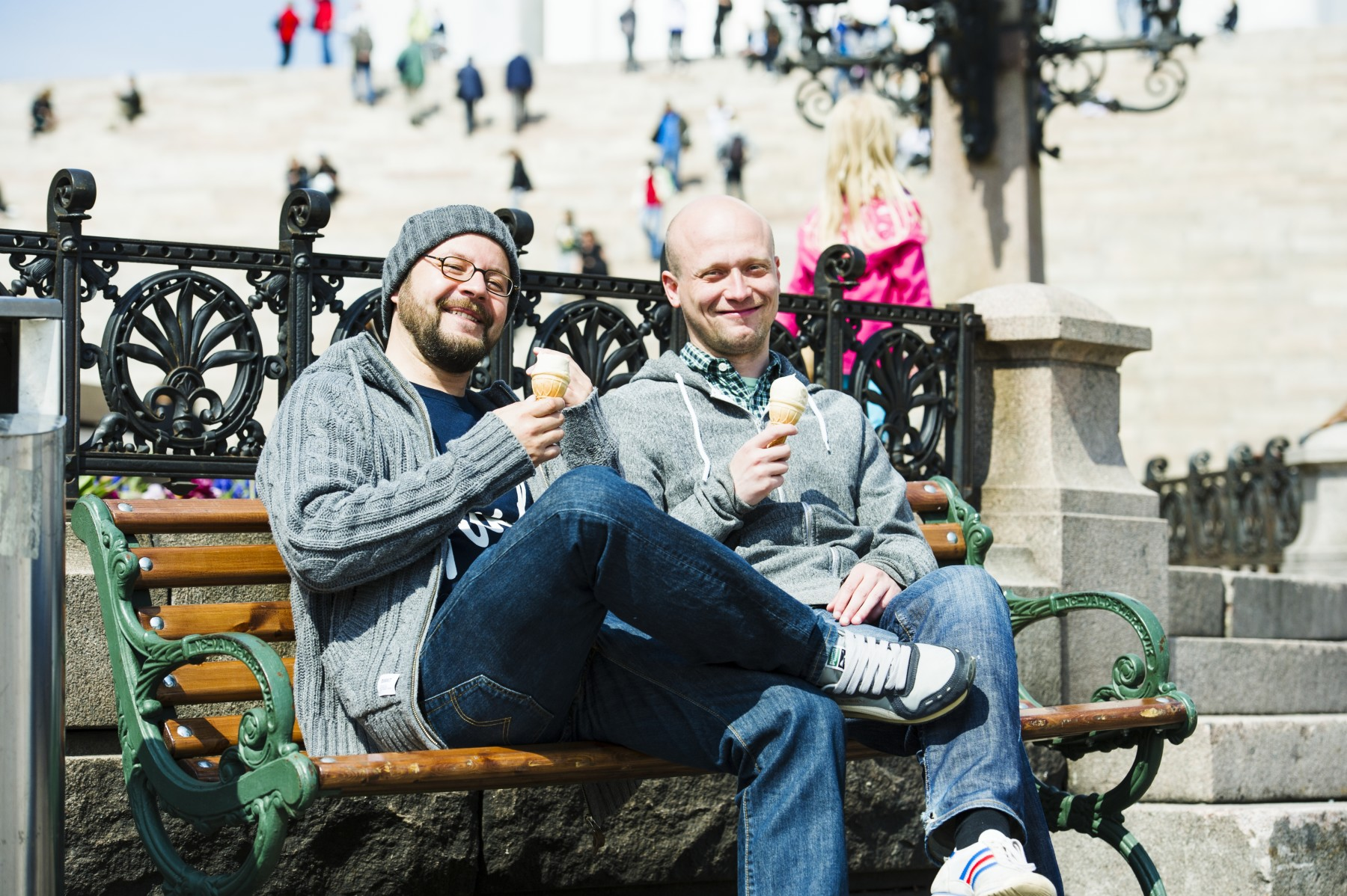 Two men sitting on a bench eating ice cream.
