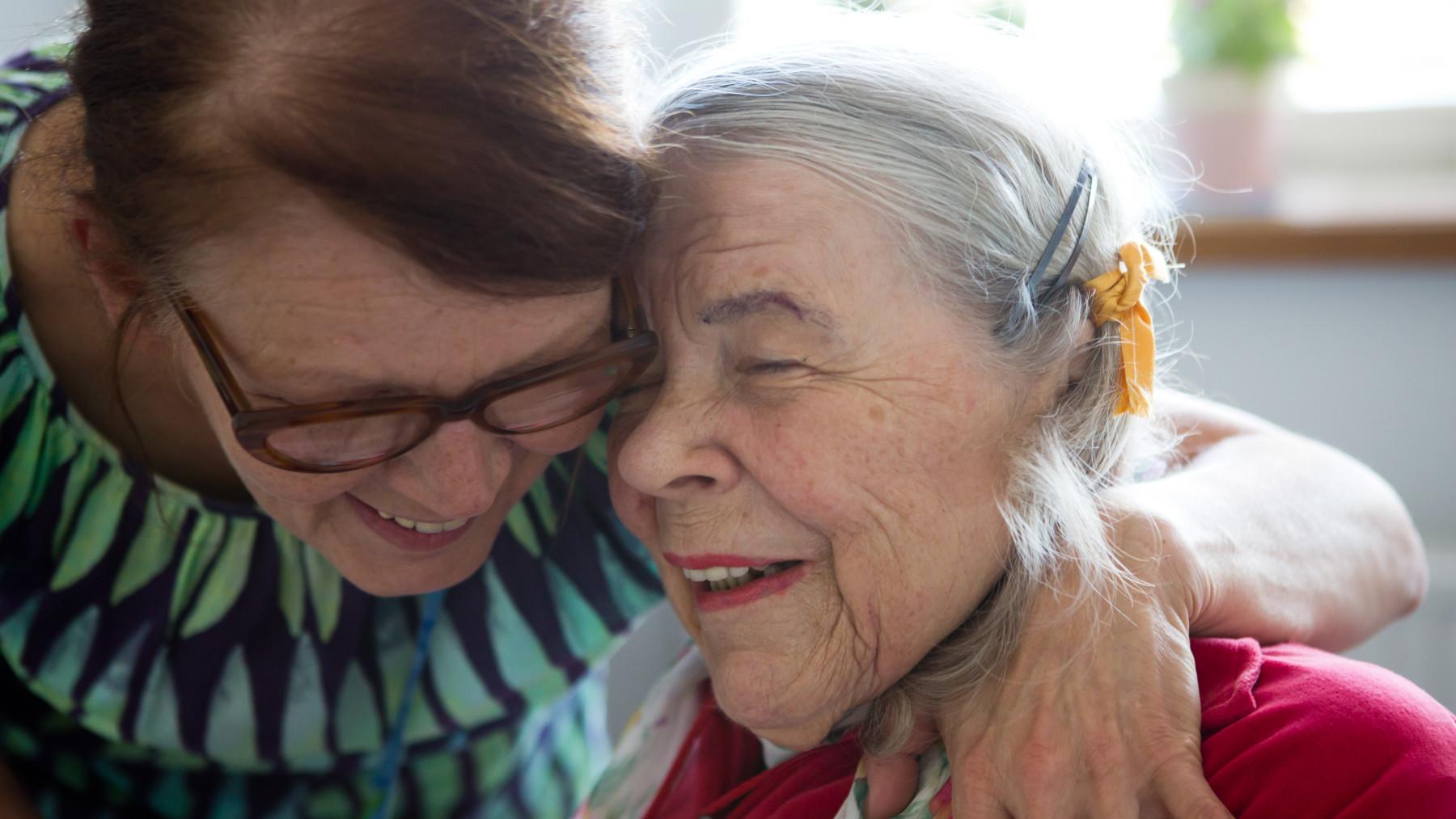 Two elderly women hugging.
