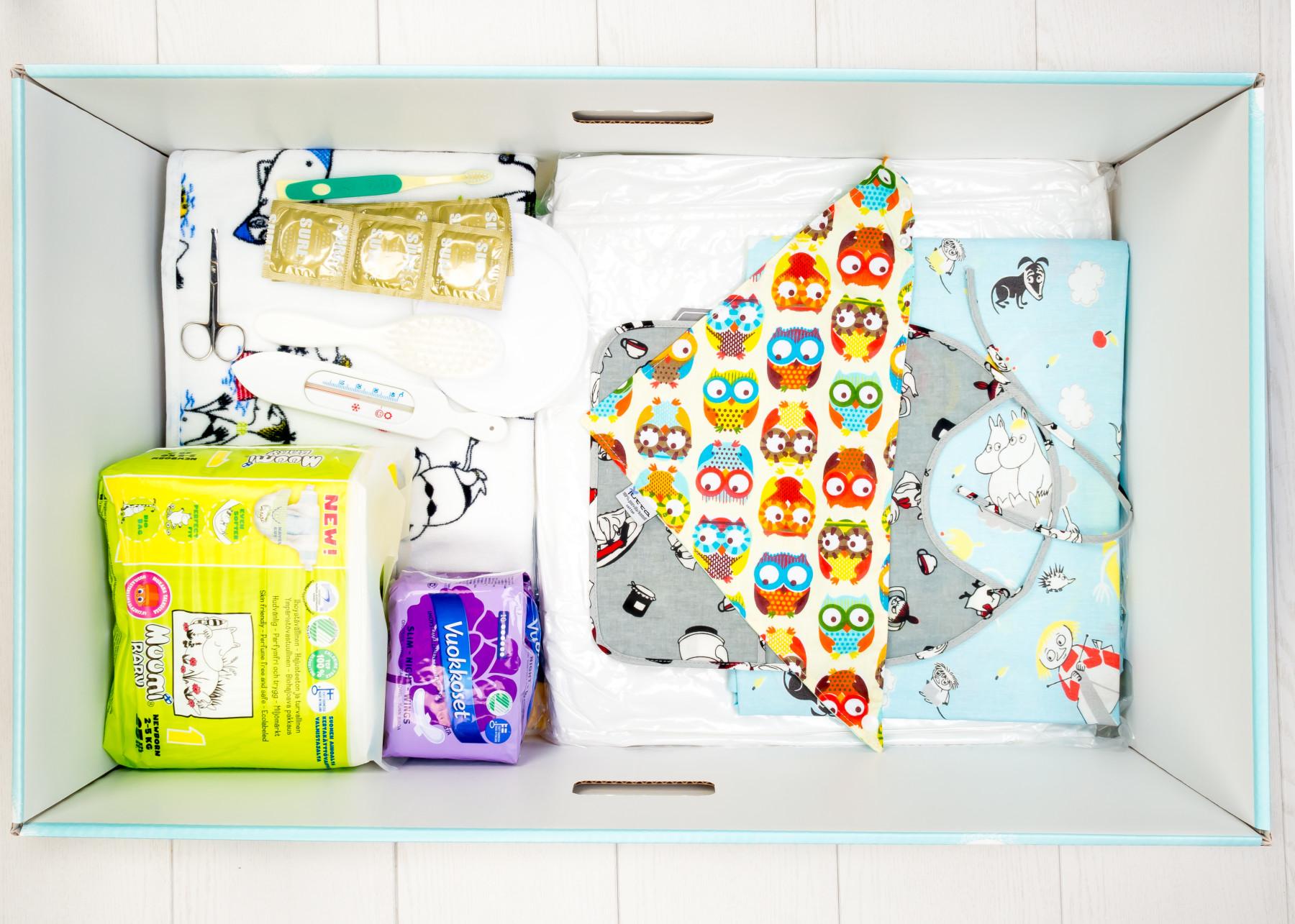 A caixa para bebês inclui, entre outras coisas, roupas, saco de dormir, lençóis, cortador de unhas, termômetro, fraldas reutilizáveis, profiláticos e um anel de dentição. Tanto a caixa para bebês quanto o pacote maternidade original também incluem preservativos.