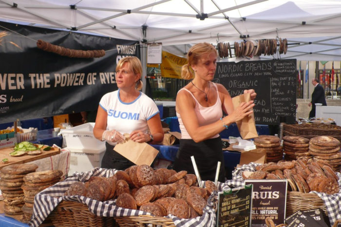 Two vendors at a market stall with piles of rye bread on sale.