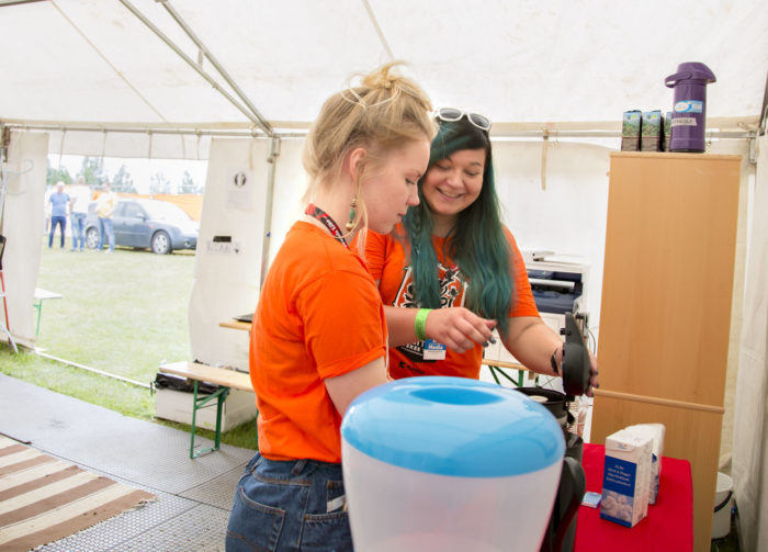 Two volunteers at Ilosaarirock retreat to a break room inside a tent for a well-deserved cup of coffee.