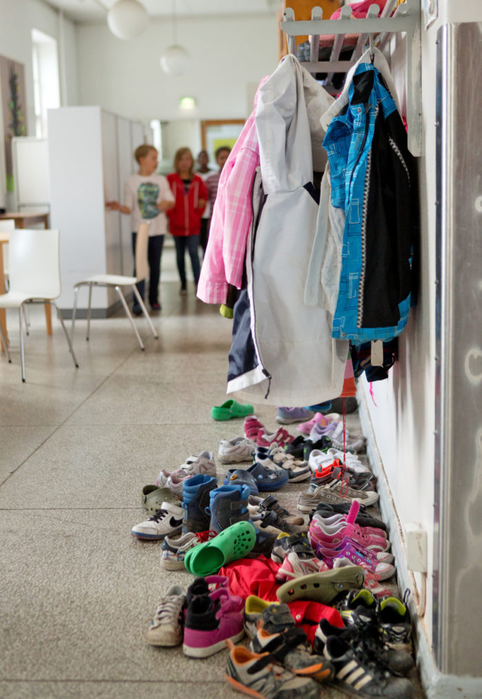 Jackets hanging from a rack; a pile of children's shoes on the floor.