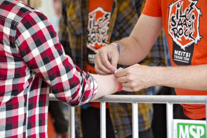 A volunteer in an orange shirt fastens an Ilosaarirock admission wristband on a plaid-clad festival-goer's arm.
