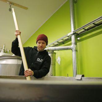 Timo Kanniainen, l'un des fondateurs de la brasserie Sonnisaari à Oulu, en train de remuer le brassin : ce mélange de malts sera ensuite laissé à fermenter.