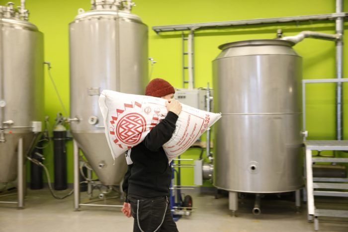 Sonnisaari cofounder Timo Kanniainen carries a 25-kilogram (55-pound) sack of malt across the brewery floor to add to the vat.