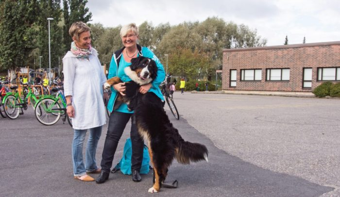 Special-needs teacher Heidi Puputti (left), Maarit Haapasaari of Hali-Koirat (Hug Dogs) and Hilma the Bernese mountain dog hang out in front of Hovirinta School.