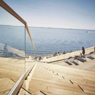 Деревянная терраса сауны Лёюлю на берегу Балтийского моря в солнечный день.