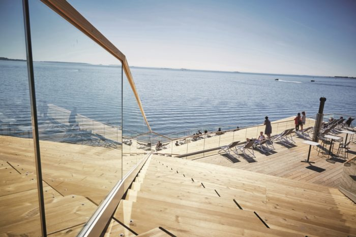 The wooden terrace of Löyly sauna in front of the Baltic Sea on a sunny day.