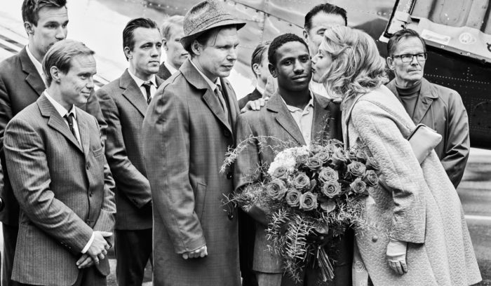 Manager Elis Ask (Eero Milonoff, wearing hat) encouraged a great deal of hype around the big boxing match between Olli Mäki (Jarkko Lahti, front left) and Davey Moore (John Bosco Jr, holding flowers).