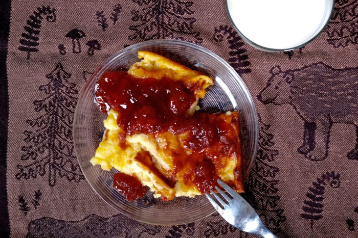 "Thick slices of oven-baked pancake are served for dessert, topped with strawberry jam. (The tea towel, called ""Metsäpolku"" (forest path), is designed by Marja Rautiainen for Lapuan Kankurit.)"