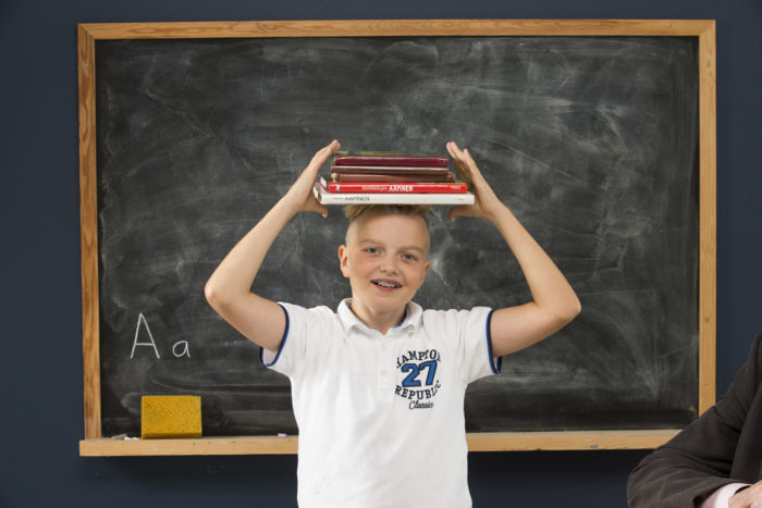 A boy balancing a stack of school books on his head.