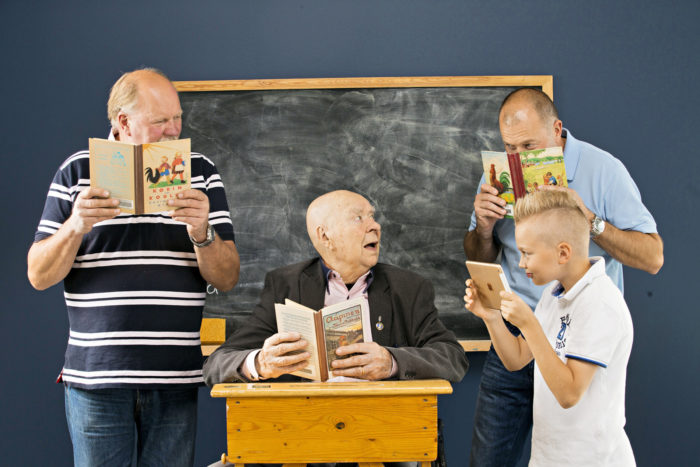 Three men and a boy reading ABC books in front of a blackboard.