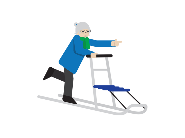 An elderly woman stands on a kicksled, pushing off with one foot and pointing forward with her left index finger.