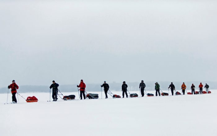 مجموعة من المتزلجين تعبر جزءًا من بحيرة سايما، ويسحبون أمتعة التزلج على زلاجات خلفهم.