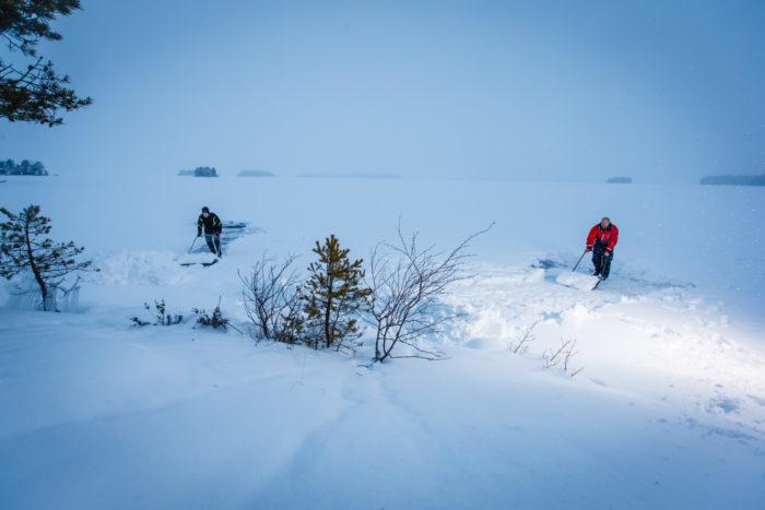 ميكو إيمونن (على اليمين) وأخوه إسا يدفعان الثلج عن سطح البحيرة المتجمد للمساعدة في حماية الفقمة في بحيرة سايما.