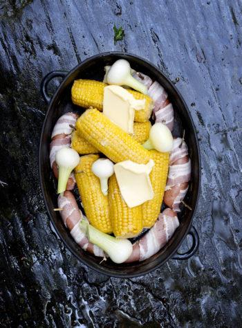 جاهز للشواء: الذرة الطازجة على قطعة من الخبز، والسجق الملفوف بلحم الخنزير المقدد، والبصل جميعها يملأ الساونا بالروائح الرائعة.