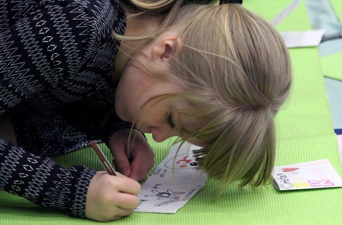 طالبة في مدرسة باسكيفوري الابتدائية مستغرقة في تأليف كتاب عن فكرة، واحد من أنشطة مشروع الإجراءات الخضراء لصفها.