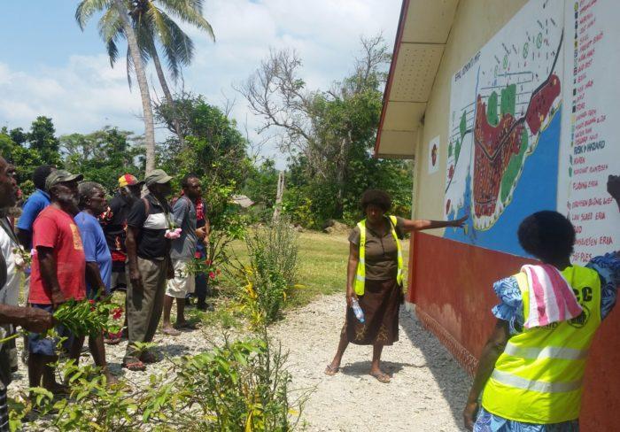 وف إيباو بفانواتو، يناقش أعضاء المجموعة خريطة للمخاطر مرسومة على حائط المدرسة المحلية، توضح المناطق التي يُحتمل فيها حدوث فيضانات وانهيارات أرضية وغيرها من المعلومات المتعلقة بخطط الإجلاء.