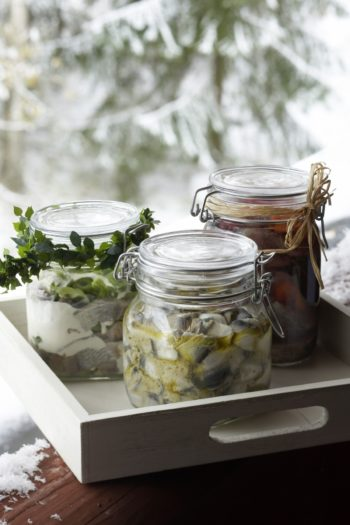 Several jars containing sliced herring sit on a tray in front of a window showing a winter landscape.