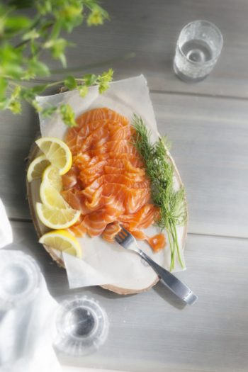 A platter contains slices of salmon and lemon, and sprigs of fresh dill.