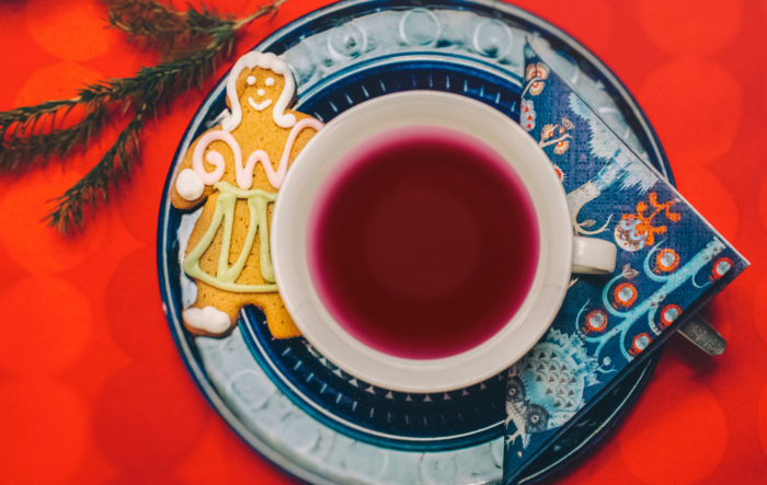 A view from above shows a cup of red liquid beside a gingerbread cookie shaped like a person.
