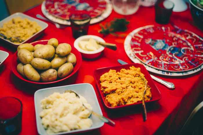 A festively decorated table has serving bowls full of vegetable casseroles and boiled potatoes.
