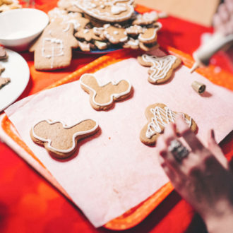 Several hands are decorating gingerbread cookies at a table.