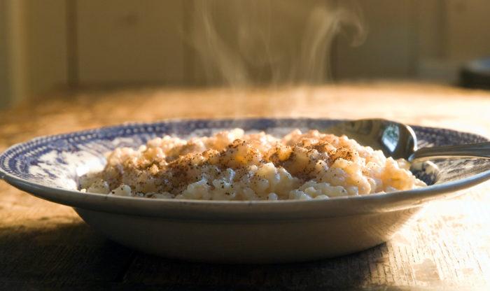 Steam rises from a bowl full of porridge.