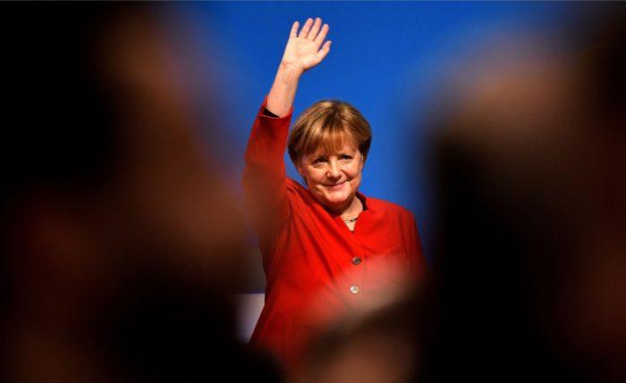 المستشارة الألمانية أنجيلا ميركل - نموذج يحتذى به لعدد لا يحصى من النساء والفتيات - تلوح للجمهور في مؤتمر الحزب.