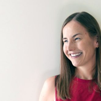 A smiling woman in a red top in front of a white wall.