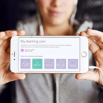 A person holding a phone with two hands, the screen says 'My learning plan'.
