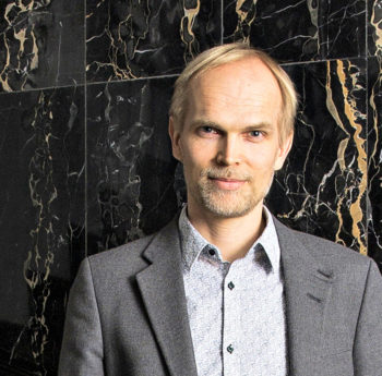 Portrait of Harri Valpola in front of a black marble wall.