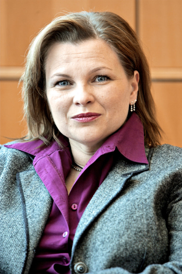 Mari Lättilä pictured in a purple shirt and a grey wool coat.