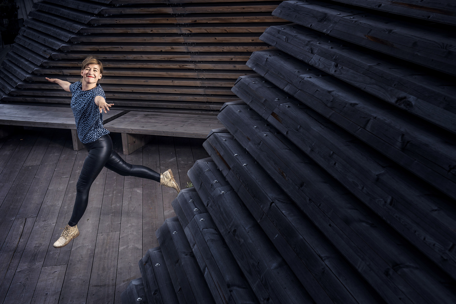 Linda Liukas jumping ballerina-like amidst dark wooden walls and floor.