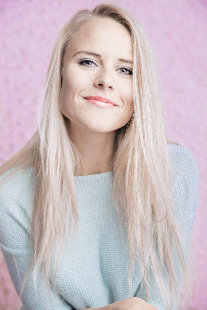 Portrait of a smiling Nelli Lähteenmäki on a pink background.