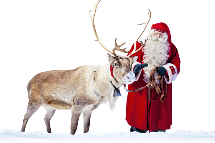 An old bearded man in red clothes with a reindeer.