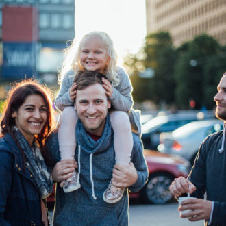 Three adults and one girl smile at the camera in front of some buildings in central Helsinki.