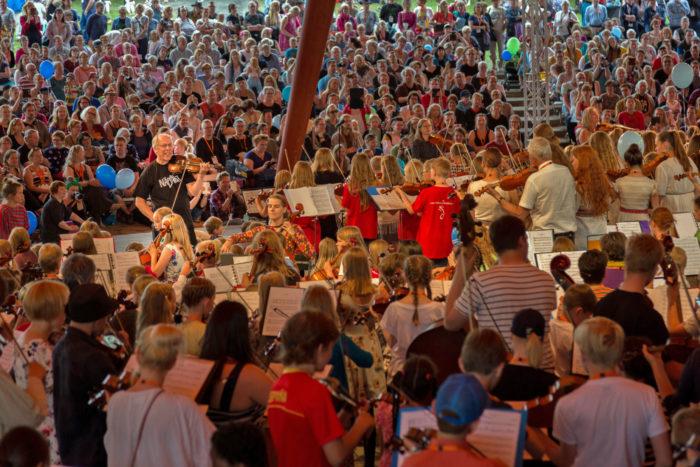 في مهرجان كوستينن للموسيقى الشعبية، العازف ومعلم الموسيقى مونو جارفيلا (في الوسط على اليسار) ومعلمون آخرون يقودون مئات الطلاب أمام جمهور كبير في المسرح الرئيسي.