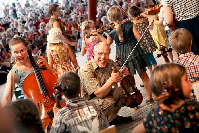 مونو جارفيلا يرفع إصبعه الإبهام قبل أن يقوم الأطفال بالعزف في عرض ناباريت في مهرجان كوستينن، ليبرهن على أن التقليد الموسيقي الذي يرجع إلى مئات السنين مستمر في سياق حديث.