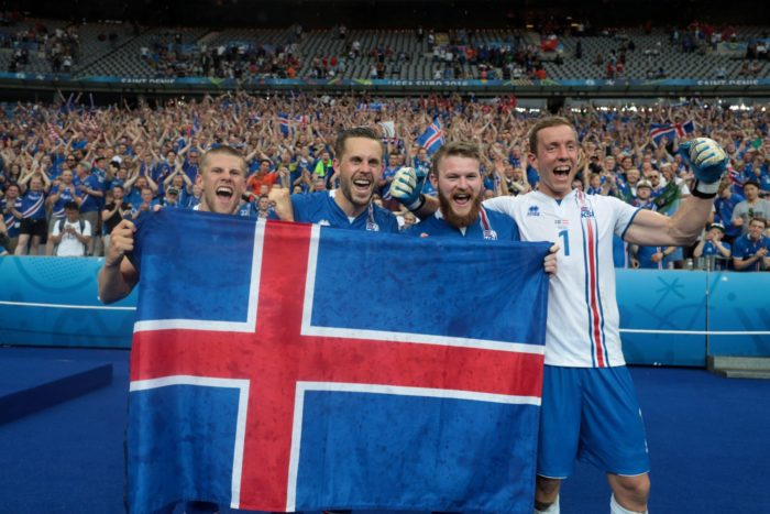 من اليسار: المهاجم الأيسلندي يوهان غودموندسون، لاعبو خط الوسط غيلفي سيغوردسون وأرون غونارسون وحارس المرمى هانيس هالدورسون يرفعون علم بلادهم بعد هزيمتهم للنمسا في بطولة أمم أوروبا 2016، حيث أعلنت أيسلندا عن وجودها بالتقدم إلى الربع النهائي من المباريات. في كأس العالم، تضم مجموعتهم الأرجنتين وكرواتيا ونيجيريا.