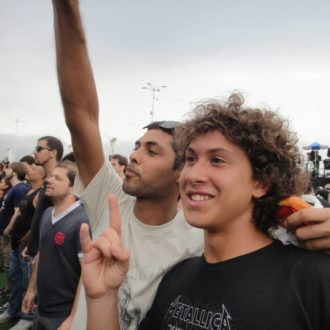 Two guys standing in a concert crowd; one has his arm raised and the other is making the sign of the horns.