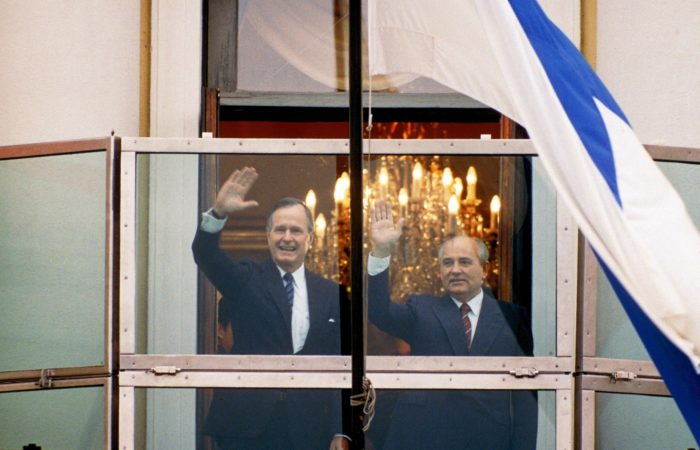 Smiling George H.W. Bush and Mikhail Gorbachev waving from a balcony.