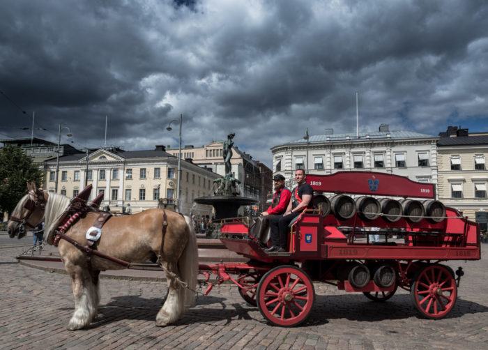 A red horse-drawn carriage in front of Havis Amanda statue in Helsinki.