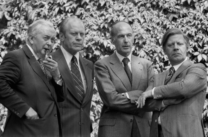 A black-and-white photo of Harold Wilson, Gerald Ford, Valery Giscard d'Estaing and Helmut Schmidt standing in front of a hedge.