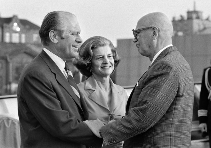 A black-and-white photo of smiling Gerald and Betty Ford shaking hands with Urho Kekkonen.